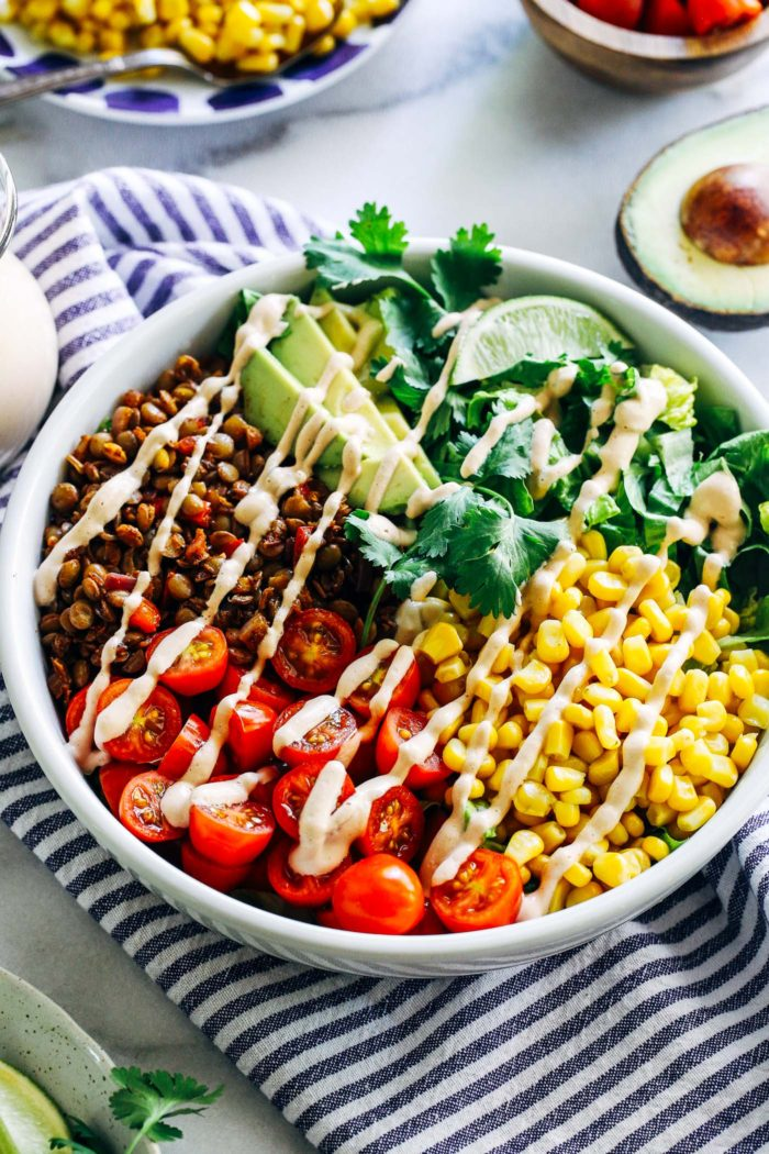 Easy Lentil Taco Salads- seasoned lentils are served on a bed of crisp romaine lettuce with juice tomatoes, sweet corn and buttery avocado. Topped with a creamy cashew salsa dressing, this salad is sure to be a new favorite! (vegan, gluten-free + grain-free with nut-free option)