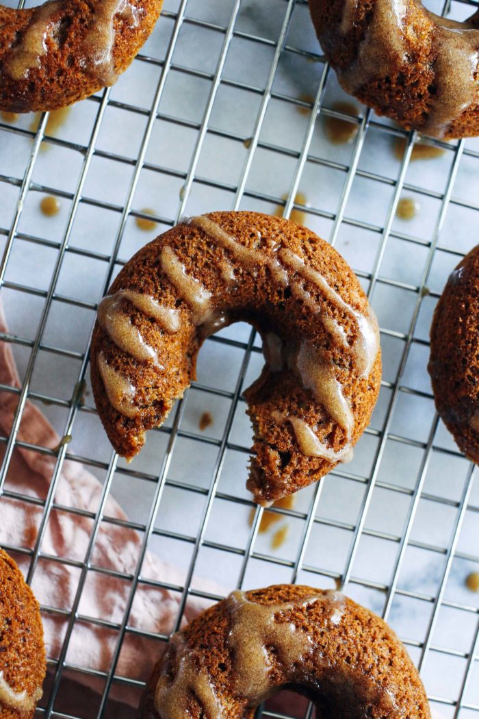 Vegan Apple Cider Donuts with Caramel Glaze- a simple mix of almond and oat flour gives these baked donuts a delicious cake-like texture. Topped with a refined sugar-free caramel glaze, they're irresistible! (vegan + gluten-free)