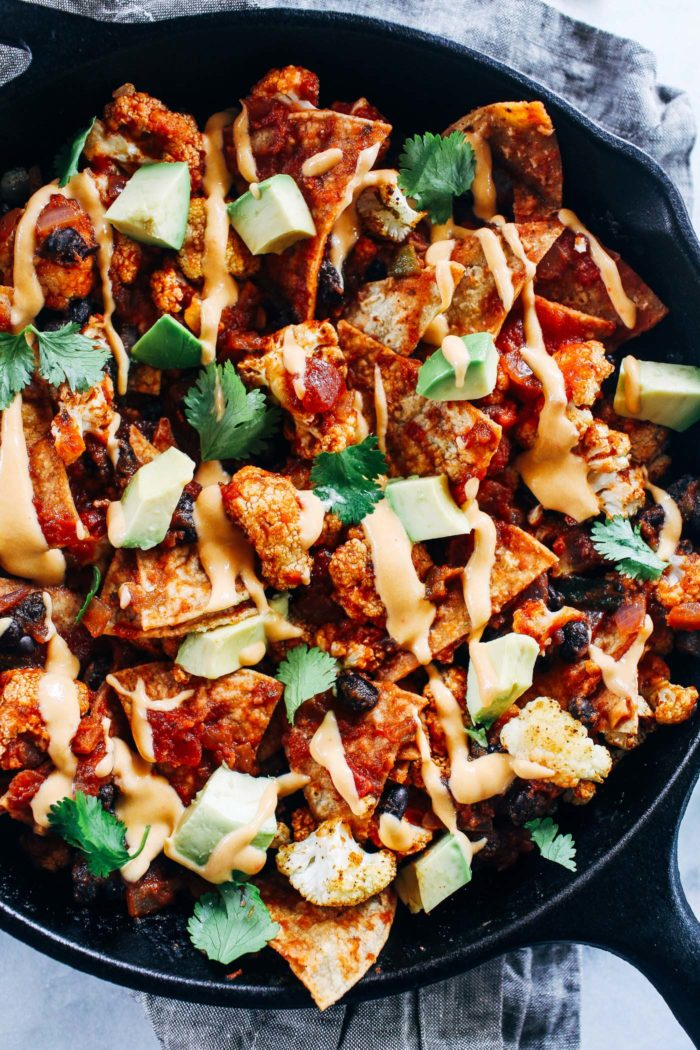 Roasted Cauliflower Chilaquiles- crispy baked tortillas are layered with roasted cauliflower, enchilada sauce, and black beans then drizzled with nacho cashew cheeze sauce. Easy to make and so delicious! (vegan + gluten-free)