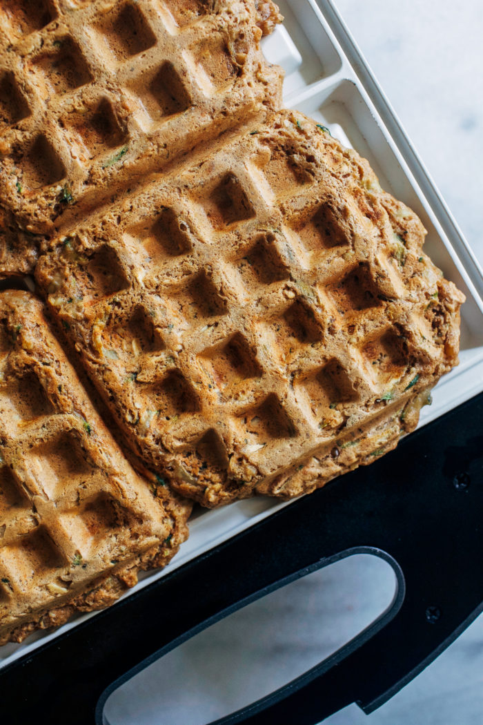 Zucchini Oat Protein Waffles- made with whole grain rolled oats, hemp seeds, almond butter and yogurt, these waffles are packed full of plant-based protein and fiber. They freeze well and are perfect to prep for busy weekday mornings! #vegan #glutenfree #healthybreakfast #waffles #plantbased #protein