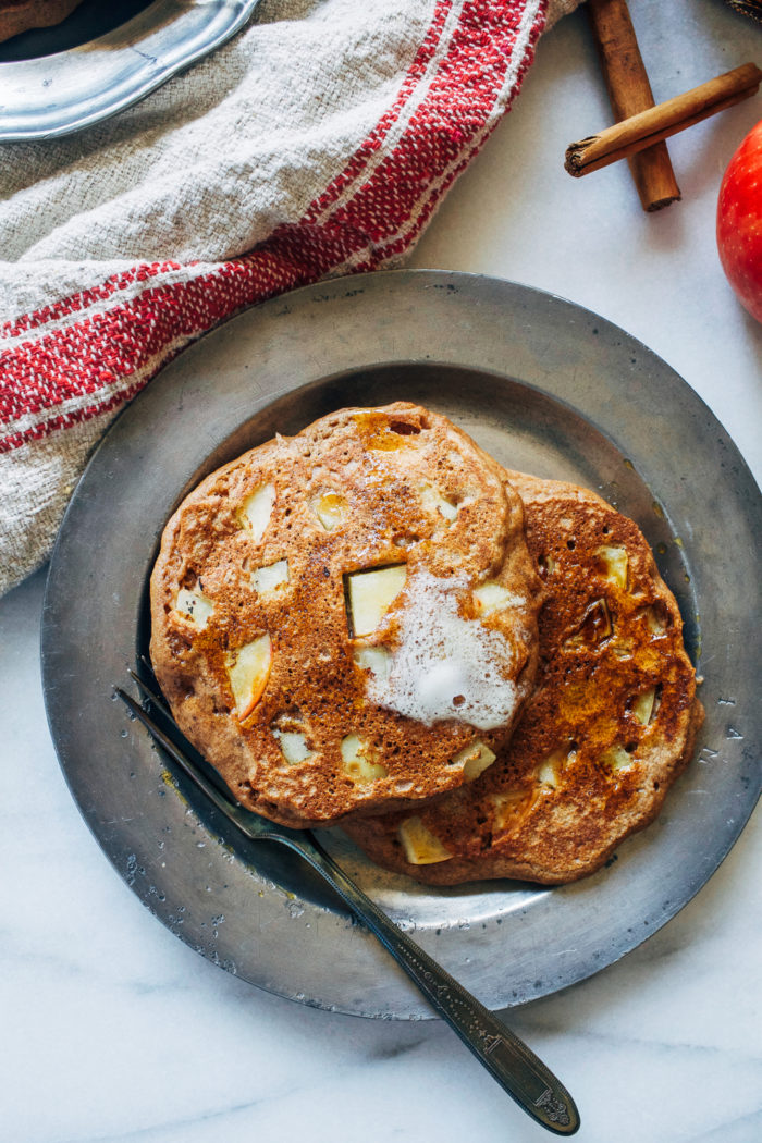 Fluffy Apple Cinnamon Pancakes- made with whole grain flour and fresh chunks of apple, these pancakes will have you jumping out of bed in the morning! #wholegrain #healthyeats #fallfood