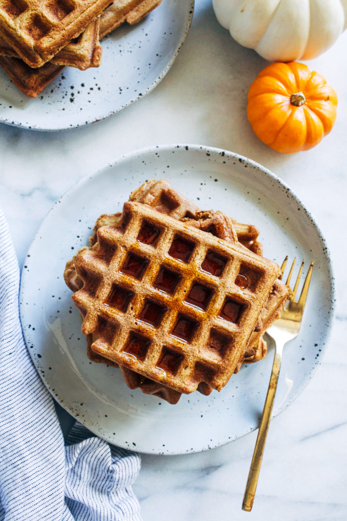 Whole Grain Pumpkin Spice Waffles- made in just one bowl, these healthy pumpkin waffles are deliciously light and fluffy. They can easily be made gluten-free and vegan too! #healthyeating #cleaneating #pumpkinrecipes #plantbased